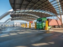Vrachtwagens krijgen instructies onder De Canopy op de Tweede Maasvlakte